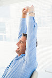 Happy businessman stretching his arms