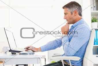 Man in shirt using laptop and thinking