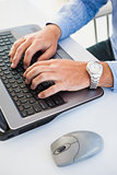 Close up of hands with wrist watch typing on laptop