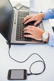 Hands typing on laptop an mobile phone in charge