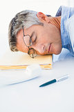 Man with glasses sleeping on his files
