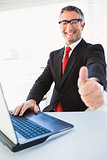 Positive businessman in suit with thumbs up