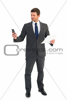 Businessman sending text holding page