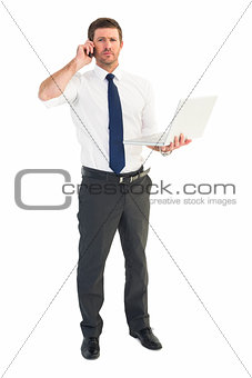 Businessman on the phone holding laptop