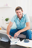 Smiling man on a laptop at home