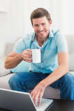 Smiling man with a mug using a laptop