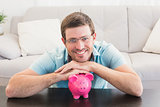 Smiling man with a piggy bank