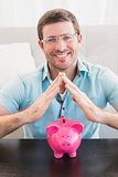 Smiling man with piggy bank