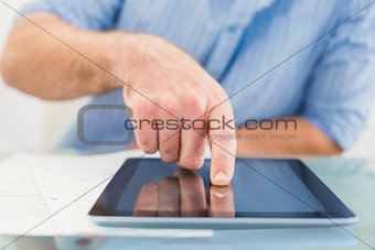 Casual businessman using tablet at desk
