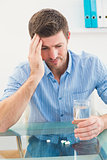 Hungover businessman holding glass of water and tablet
