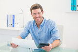 Smiling businessman working on his finances at his desk