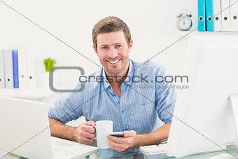 Smiling businessman holding mug and phone