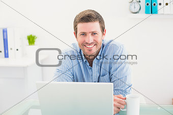 Smiling businessman holding mug at desk