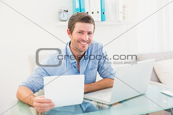 Smiling businessman holding document