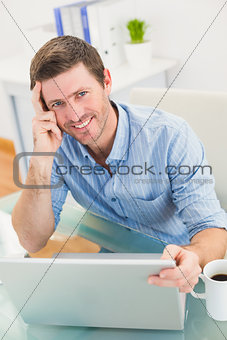 Smiling businessman using his laptop at desk