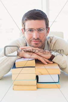 Casual businessman with books at his desk