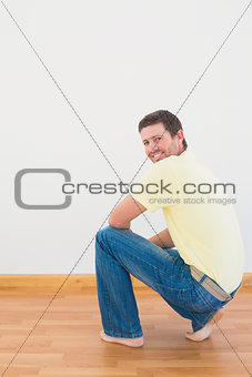 Casual man crouching on floor looking at wall at home
