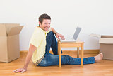 Casual man sitting on floor using laptop on the coffee table at home