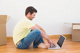 Casual man sitting on floor using laptop at home