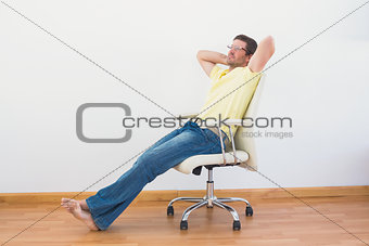 A man leaning back in swivel chair at home