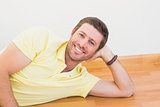 Smiling man lying on the floor at home