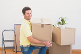 Smiling man carrying cardboard moving boxes at home