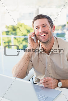 Smiling businessman making a call at his desk