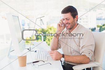 Smiling businessman making a call and reading a document