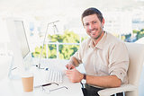 Smiling businessman looking at document at his desk