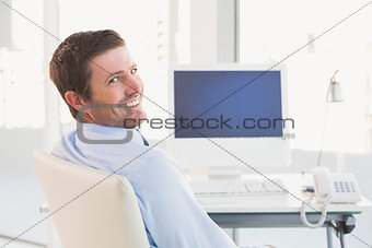 Smiling businessman sitting at his desk