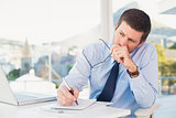 Worried businessman writing on is notepad