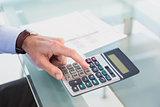 Businessman pushing key on calculator