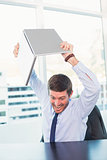 Angry businessman throwing his laptop