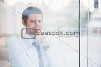 Smiling businessman looking out the window