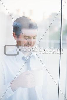 Smiling businessman holding mug seen through window