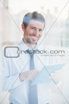Smiling businessman using tablet looking out the window