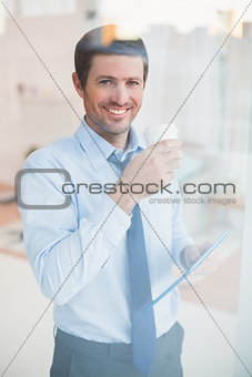 Smiling businessman holding tablet and disposable cup looking out the window