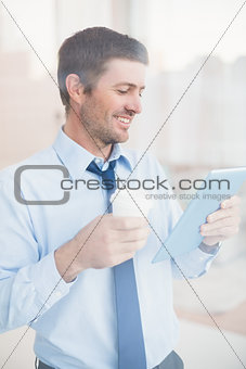 Smiling businessman using tablet holding disposable cup seen through window