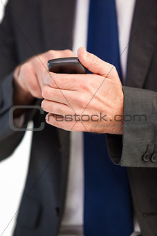 Focused businessman texting on his mobile phone