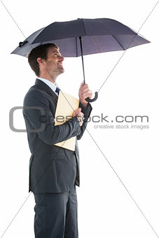 Smiling businessman holding a file under umbrella