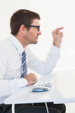 Businessman sitting at his desk pointing something
