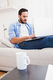 Man lying on sofa using laptop
