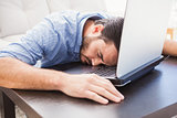 Man sleeping with head resting on laptop keyboard