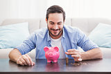 Smiling businessman putting coins into piggy bank