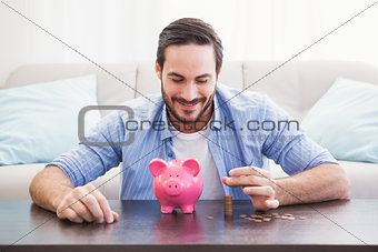 Smiling businessman putting coins into piggy bank