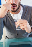 Mid section of a man with glass of water and pill