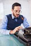 Businessman with pipe in his mouth working on typewriter
