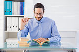 Focused businessman reading book at desk