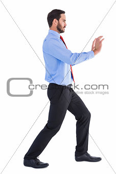 Focused businessman standing and pushing with hands
