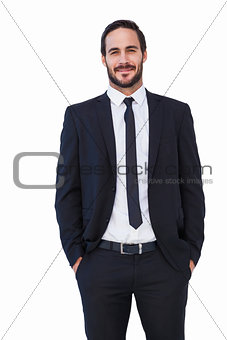 Smiling businessman in suit standing with hands in pockets